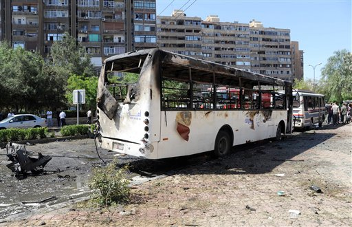 This photo released by the Syrian official news agency SANA, shows Syrians inspecting a damaged car at the scene of a car bomb exploded in the capital's western neighborhood of Mazzeh, in Damascus, on Monday. State-run Syrian TV says Prime Minister Wael al-Halqir has escaped unhurt in an assassination attempt when a bomb went off near his convoy.