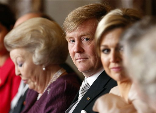 Dutch Queen Beatrix, left, looks down as she prepares to sign the Act of Abdication in favour of her son, Prince Willem-Alexander, center, who sits next to his wife Princess Maxima in the Mozeszaal or Mozes hall of the Royal Palace in Amsterdam, The Netherlands on Tuesday. A million people were expected to descend on the Dutch capital for a huge street party to celebrate the first new Dutch monarch in 33 years.