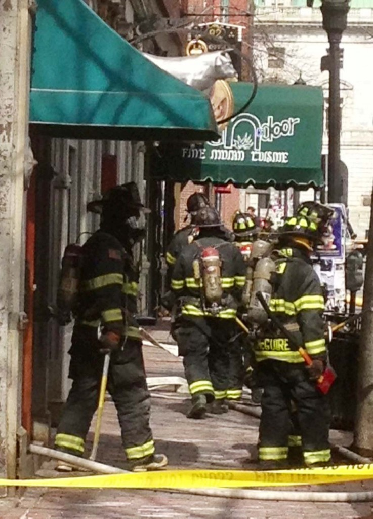 Firefighters leave the building at 86 Exchange St. in Portland where a fire broke out on Monday morning.