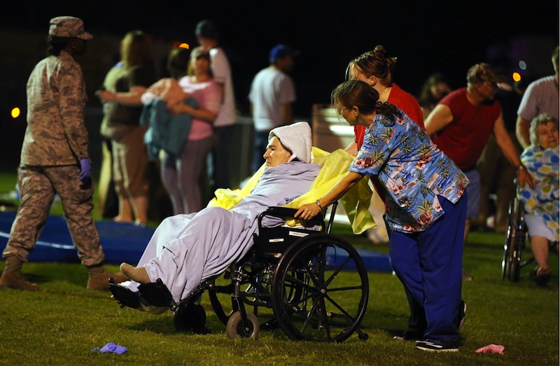 Emergency workers assist an elderly person at a staging area at a local school stadium Wednesday in West, Texas, following an explosion at a fertilizer plant near Waco.