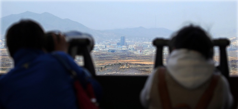 Visitors look at the North-South Korea industrial complex in Kaesong through binoculars at Dora Observation Post in the demilitarized zone (DMZ) near the border village of Panmunjom, Tuesday, April 9, 2013.The massive industrial park the rival Koreas have jointly run for nearly decade was a virtual ghost town Tuesday, its South Korean managers left to wander past shutdown assembly lines or stuff their cars to the brim with whatever goods would fit before heading south for the Demilitarized Zone that divides the nations. (AP Photo/Won Dae-hyun) Korea Out