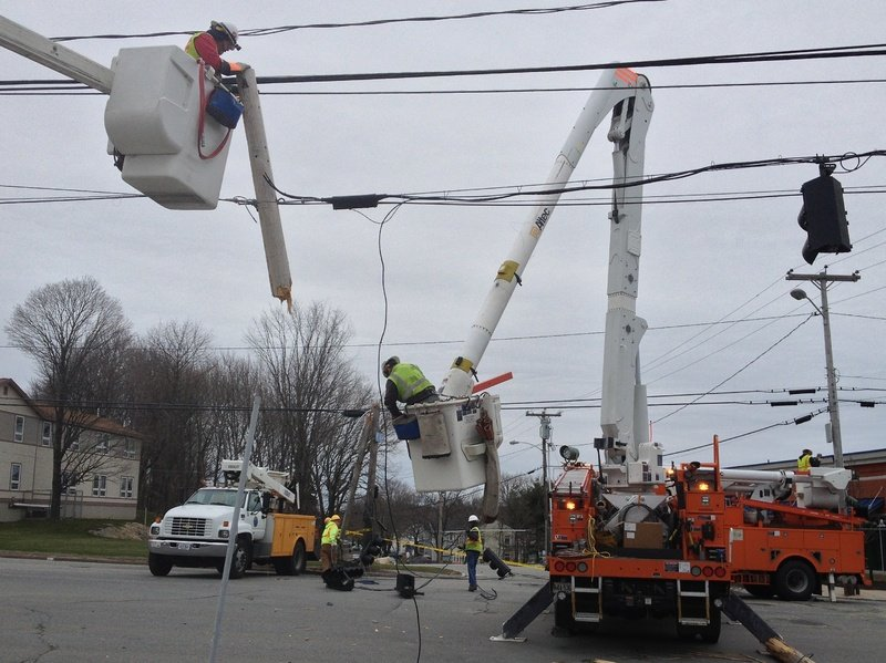 Utility workers repair damage after a tractor-trailer truck hit overhead wires and tore them down, along with the poles to which they were attached, on Brighton Avenue in Portland on Friday. The accident occurred at the intersection with Taft Avenue.