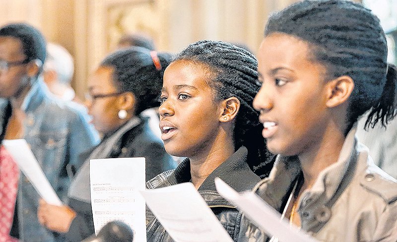 Rolande Ayinkamiye, left, and her sister Olga Ramesha sing with the Les Voix des Anges choir during the Sunday Mass. Around 25 men and women, most from Central African countries, sing in four different languages.
