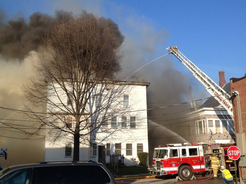 Firefighters pour water on a burning building in Lewiston on Monday. Multiple buildings were on fire.
