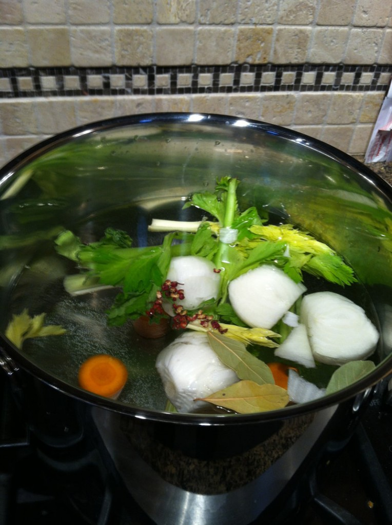 Leftover vegetables and bones simmer in a stock pot.