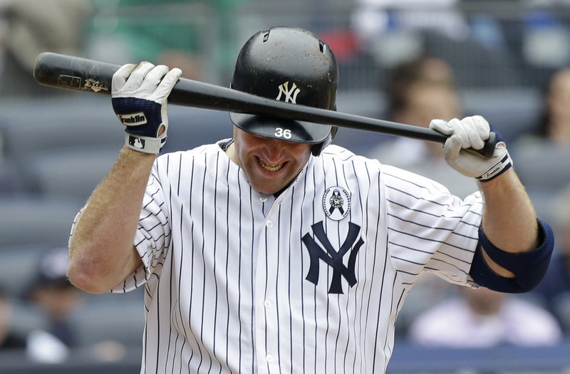New York's Kevin Youkilis knocks the bat against his helmet in frustration after striking out in the seventh and stranding two runners against his former team.