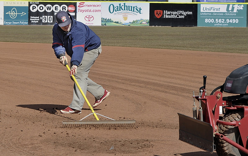 The snow has been cleared, summer is on the way and Jason Cooke, the assistant head groundskeeper, works on the infield to prepare for the opener.