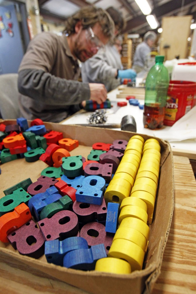 A worker assembles wooden toys at the Maple Landmark factory in Middlebury, Vt. Michael Rainville started the company and now employs his sister, wife, mother and grandmother, 93.