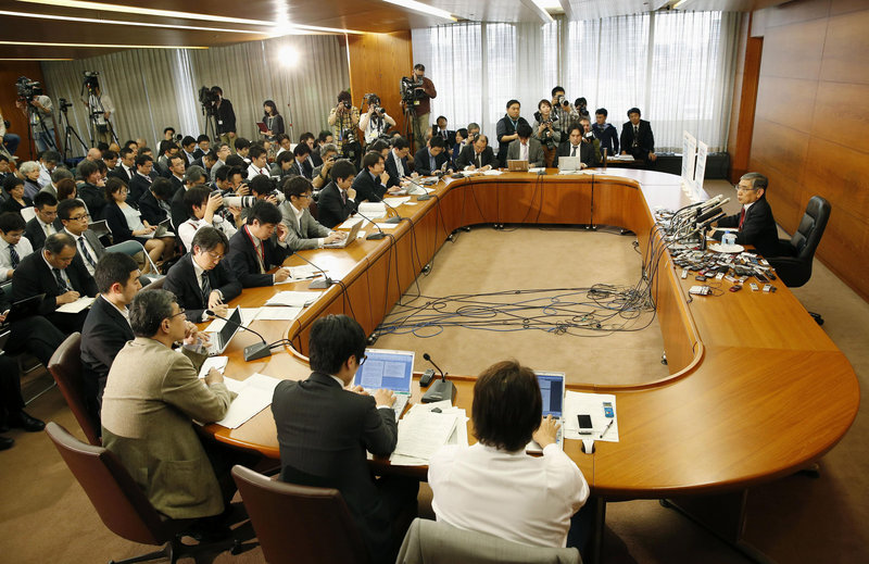 Bank of Japan Gov. Haruhiko Kuroda, right, speaks at a news conference at Japan's central bank headquarters in Tokyo on Thursday. Japan is making a sweeping shift in its monetary policy, aiming to spur inflation.