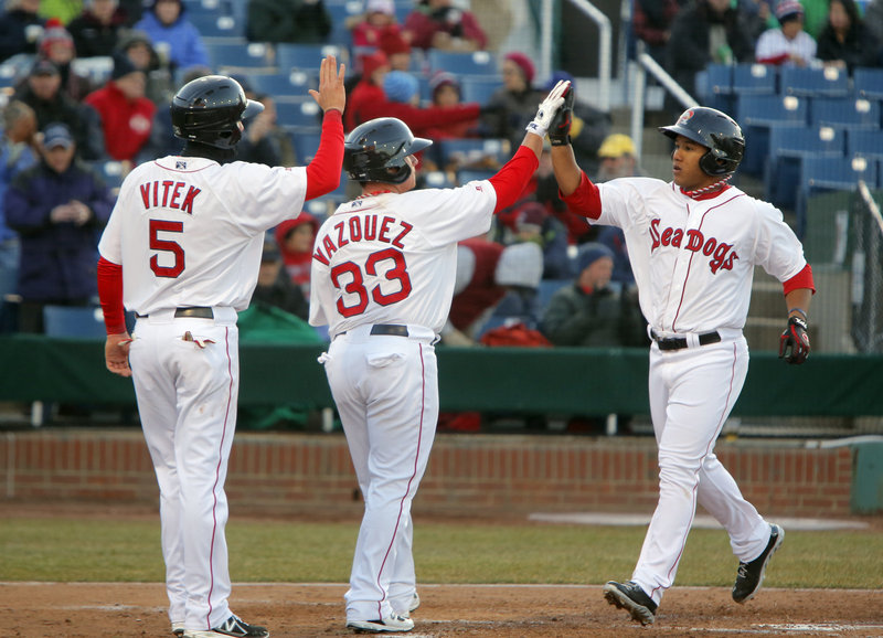 Heiker Meneses, right, is congratulated by Christian Vazquez and Kolbrin Vitek after hitting a three-run homer Thursday night for the Portland Sea Dogs in the second inning of a 13-5 loss to Trenton to open the season.