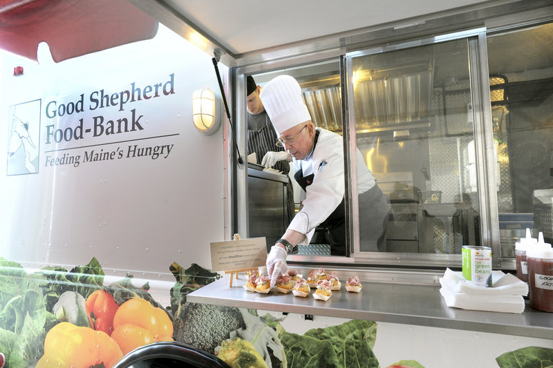 Wilfred Beriau, retired chair of the Southern Maine Communty College culinary department, serves appetizers from the Good Shepherd Food-Bank's new food truck. The occasion was the food bank's annual gala at its warehouse in Auburn, where the truck was christened by chefs Rob Evans, below left, and Karl Deuben.