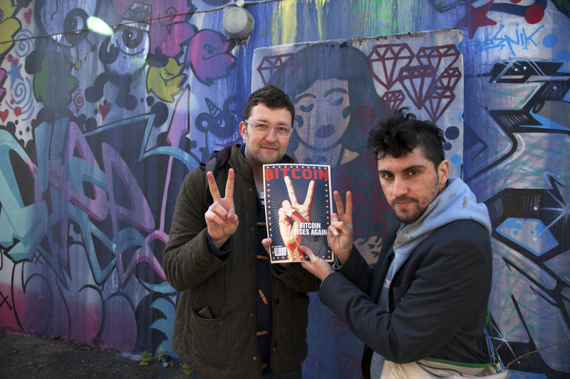 Jonathan Harrison, left, and Amir Taaki hold a copy of Bitcoin magazine in London. Harrison quit his job as a gold trader and has seen his bitcoin portfolio grow quickly in recent weeks.