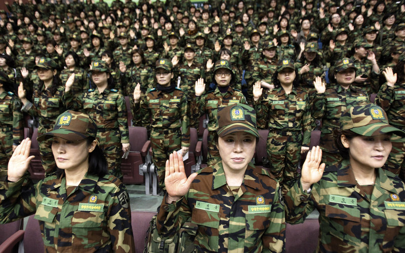South Korean army reservists raise their hands to adopt a resolution against North Korea during a rehearsal for their Foundation Day ceremony at a gymnasium in Seoul on Friday. About 1,000 reservists denounced North Korea for its escalating threats of war.