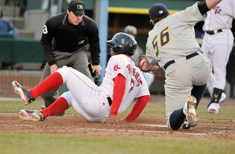 Xander Bogaerts of the Portland Sea Dogs slides across the plate Friday night, scoring on a wild pitch as Trenton pitcher Zach Nuding covers during Portland's 7-4 victory at Hadlock Field. The plate umpire is Nick Mahrley.