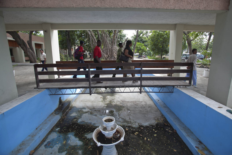 People use a pedestrian bridge at the entrance to Haiti's main courthouse, which was renovated by Chemonics International Inc., a for-profit firm based in Washington, D.C.