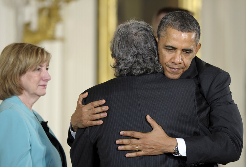 President Obama hugs Gilles Rousseau, father of slain Sandy Hook Elementary School teacher Lauren Rousseau, as her mother, Terry Rousseau, stands at left during a White House ceremony in Washington in February. Families of the school shooting victims have coalesced into a lobbying voice.