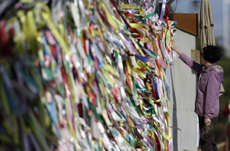 A woman reads messages on ribbons Sunday left by visitors to the Imjingak Pavilion near the border village of Panmunjom, South Korea, expressing their wishes for the reunification of the two Koreas. North Korea last week suggested diplomats leave the country.