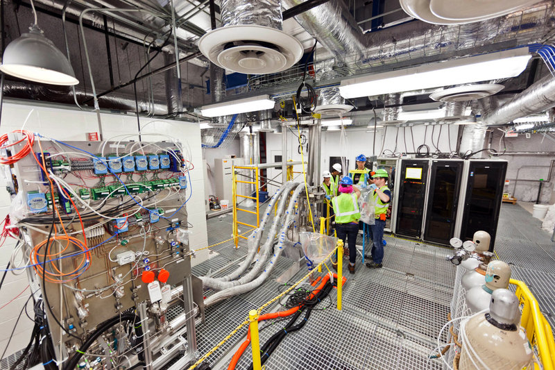 In a photo provided by Sanford Lab, researchers work on the top floor of the Large Underground Xenon experiment at a shuttered gold mine in Lead, S.D.