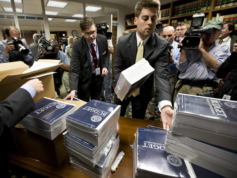 Copies of President Obama's budget plan for fiscal year 2014 are distributed to Senate staff on Capitol Hill in Washington on Wednesday.