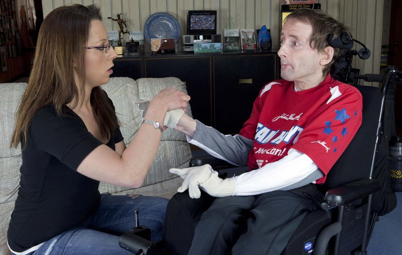 In this April 5, 2013, photo, Rick Hoyt's personal caregiver Lori Templeman, left, helps him put on gloves at his home in Holland, Mass. Hoyt's father Dick has pushed Rick, who is a quadriplegic and has cerebral palsy, in a specially designed wheelchair along the 26.2-mile Boston Marathon route for more than 30 years. They plan to compete again in Monday's race.