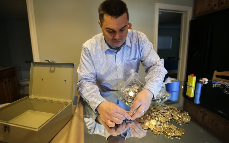 Mike Caldwell, a 35-year-old software engineer, looks over bitcoin tokens at his shop in Sandy, Utah. Caldwell mints physical versions of bitcoins, cranking out homemade tokens with codes protected by tamper-proof holographic seals.
