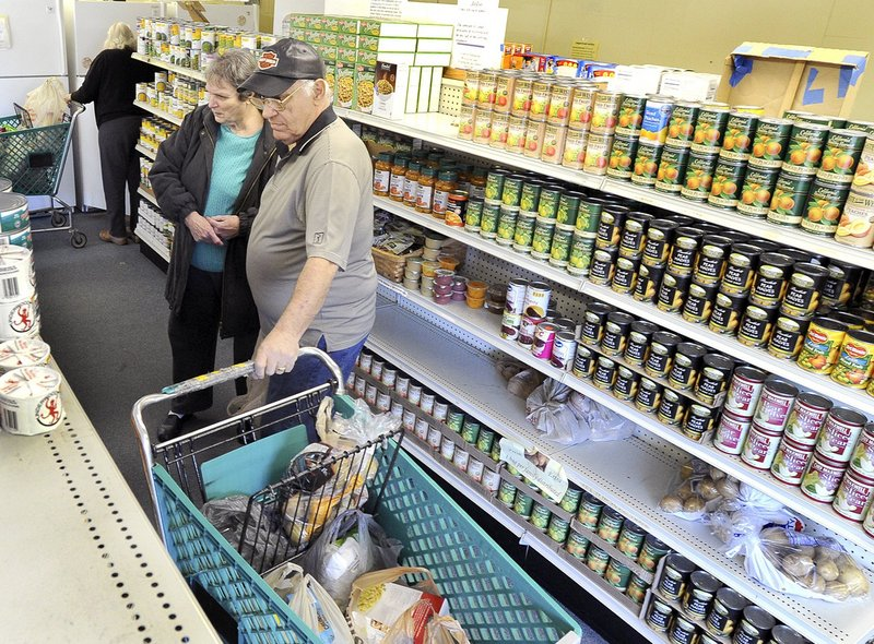 Volunteer George Coburn helps Eleanor Locey of Saco select groceries at the Saco Food Pantry last month. Churches and nonprofit aid agencies are facing unprecedented demand for help from people who can't afford to feed themselves adequately.