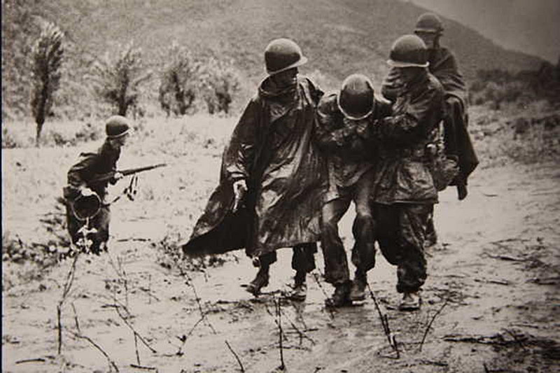 Image provided by the Army shows chaplain Capt. Emil J. Kapaun, right, and Capt. Jerome A. Dolan, a medical officer with the 8th Cavalry Regiment, carrying an exhausted soldier off a battlefield during the Korean War in November 1950.