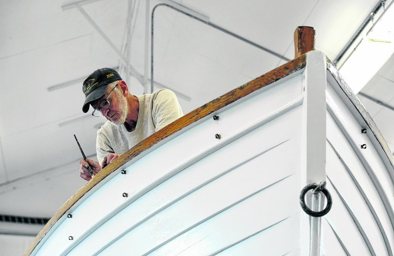 Volunteer Don St. Pierre paints a former Coast Guard motorized surfboat on March 28 that is being restored at Coast Guard Station Chatham in Massachusetts.
