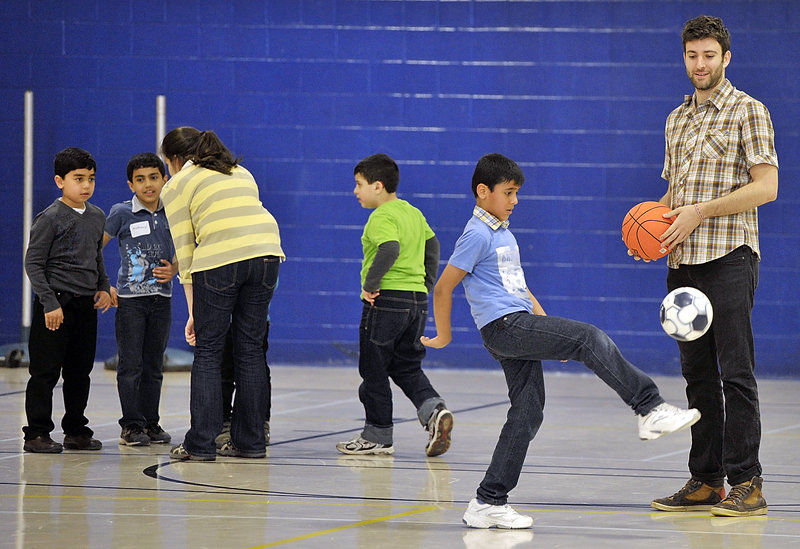Jake Acker watches as Omar Jashaami shows off his soccer skills, while another volunteer works with a group of children during New Mainers' Day at the Sullivan Recreation and Fitness Complex on the University of Southern Maine's campus in Portland on Saturday.