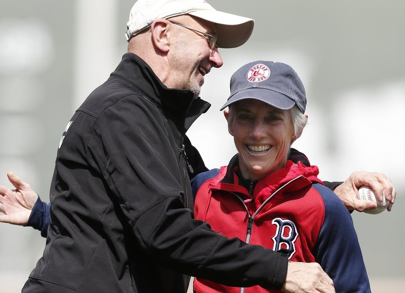 Joan Benoit Samuelson gets a hug Saturday from Greg Meyer after they threw out the first pitch at Fenway Park, celebrating the 30th anniversary of their 1983 Boston Marathon wins.