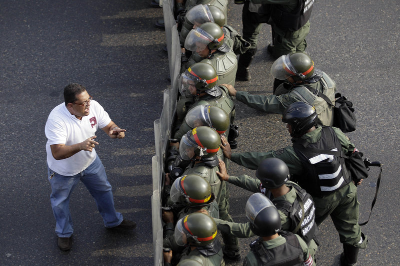 A man confronts riot police along a highway in Caracas, Venezuela, on Monday. Troops fired tear gas and plastic bullets to disperse students protesting presidential election results.