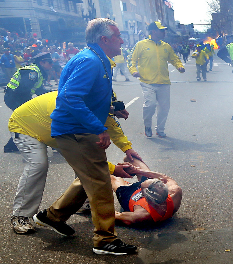 People react to the second explosion near the finish line of the Boston Marathon Monday.