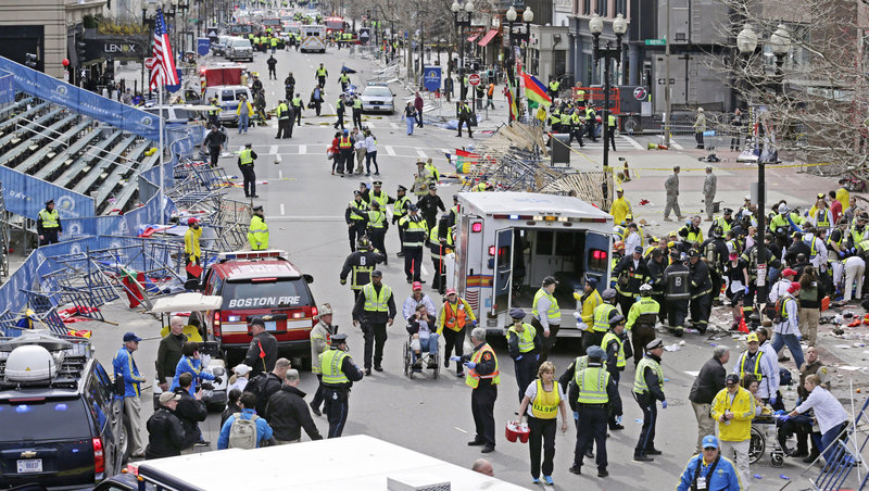 Emergency responders tend to injured people at the finish line of the Boston Marathon after Monday's explosions. Three people were killed and more than 140 were injured.