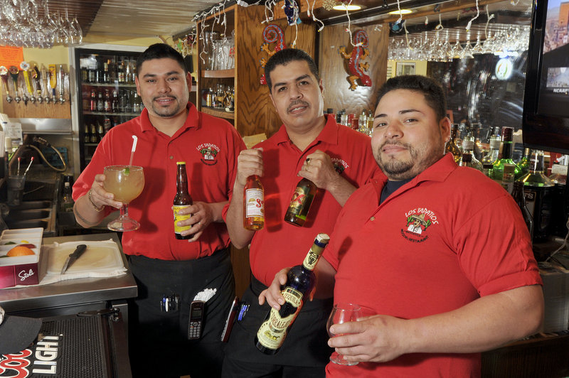 Manager Gama Chavez with staff members Juan Lozano and Ocho Chavez display some of the drink options at Los Tapatios on Adams Street in Biddeford, including the large margarita.