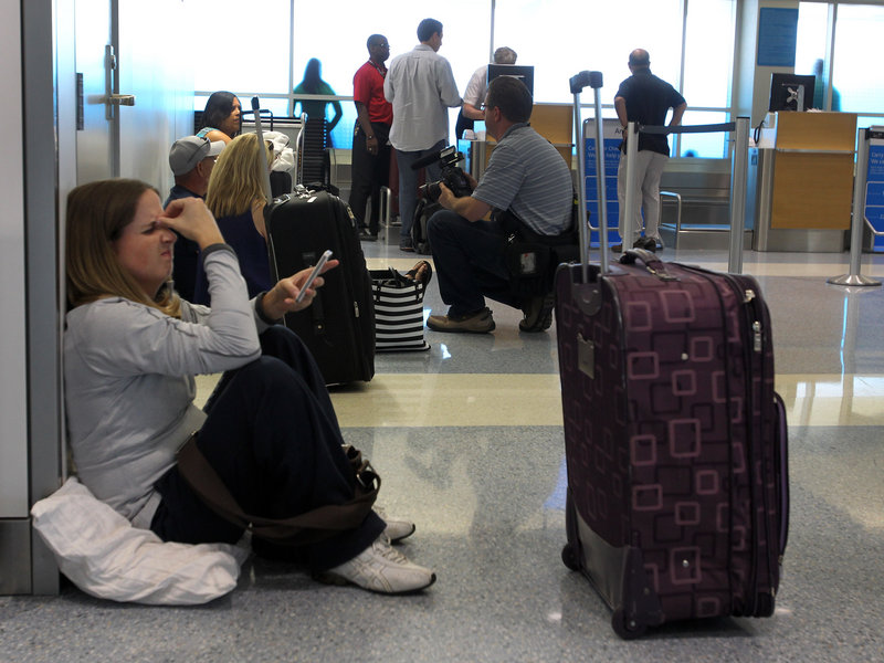 Stranded passenger Alexis Bennett waits for her flight to Chicago in Terminal A at Dallas-Fort Worth International Airport on Tuesday. American Airlines grounded flights across the country because of an outage in its main reservations system. Thousands of passengers were stranded across the country.