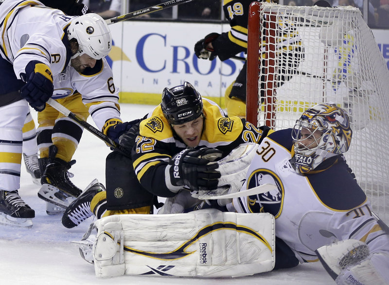 Boston right winger Shawn Thornton (22) falls onto Buffalo goalie Ryan Miller while defenseman Mike Weber (6) lunges for the puck Wednesday night in Boston.