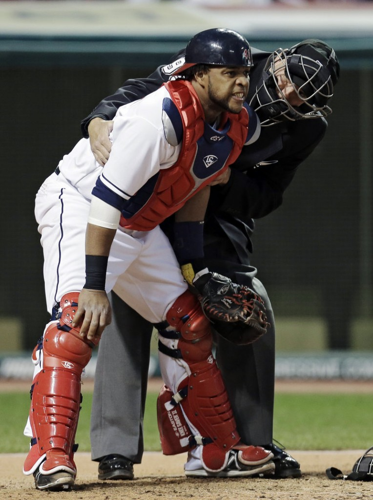 Umpire Tim Timmons tends to Cleveland catcher Carlos Santana after he was hit by a foul tip off the bat of Boston's Dustin Pedroia in the fourth inning Wednesday night.