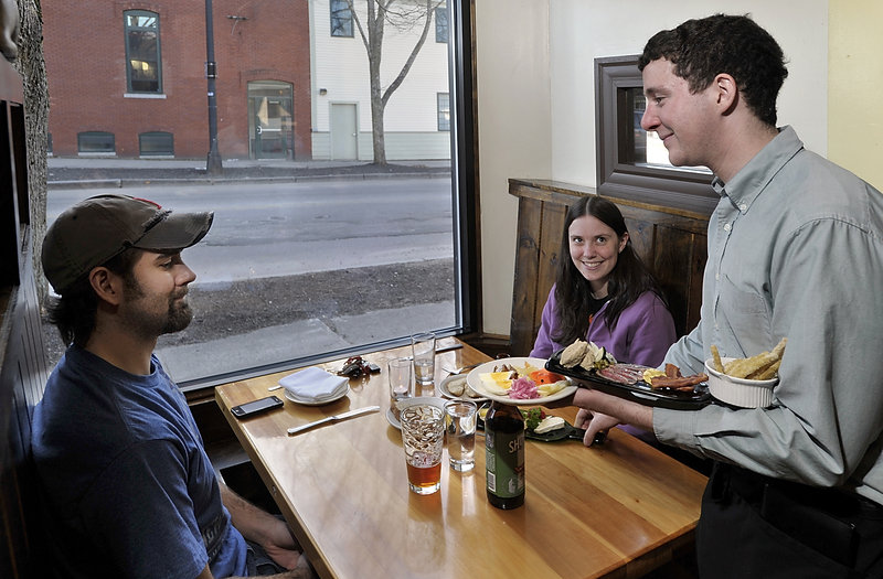 Walter Noah Tipton serves cheese and charcuterie platters to Allen and Amanda Conant at the Frog and Turtle in Westbrook.