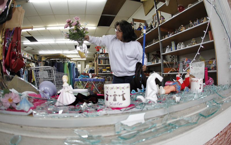 Maria Galvan sorts through damaged merchandise inside the West Thrift Shop on Thursday.