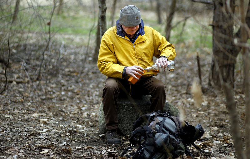David Belibeau pours himself a beer in the woods of West Commercial Street, where homeless camps are being cleared after a man perished in a tent fire earlier this month.