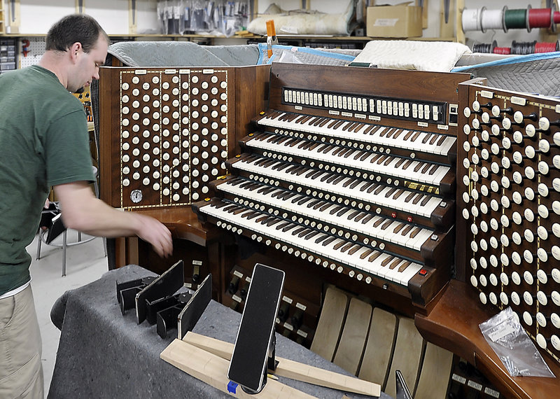 "Adam Loagocki works on the console of Portland's Kotzschmar Organ. He is part of a team of experts who will make the organ ""sing"" again."