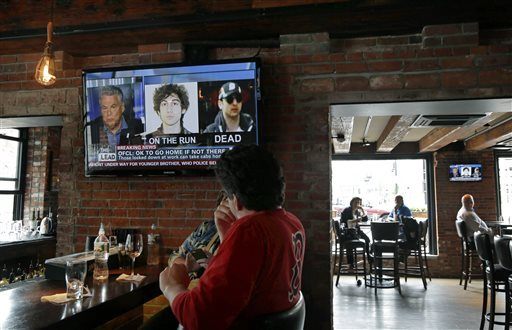 Customers watch the news at the Granary Tavern in Boston on Friday. Two suspects in the Boston Marathon bombing killed an MIT police officer, injured a transit officer in a firefight and threw explosive devices at police during their getaway attempt in a long night of violence that left one of them dead and another still at large Friday.