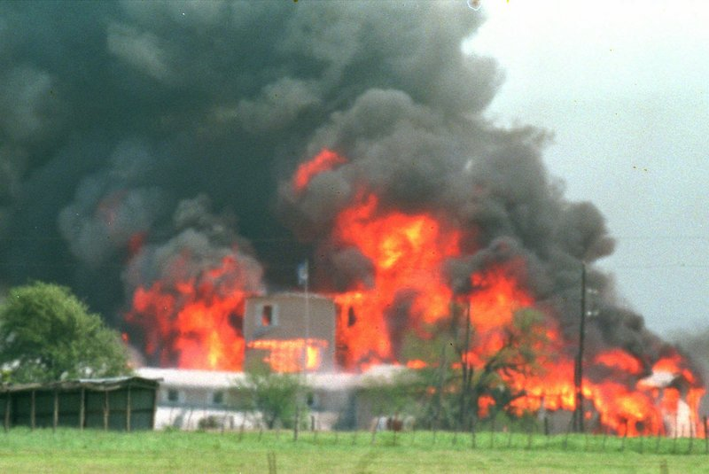 Fire engulfs the Branch Davidian compound near Waco, Texas, in this April 19, 1993, file photo. Some who survived the end to the 51-day standoff had a memorial service Friday.
