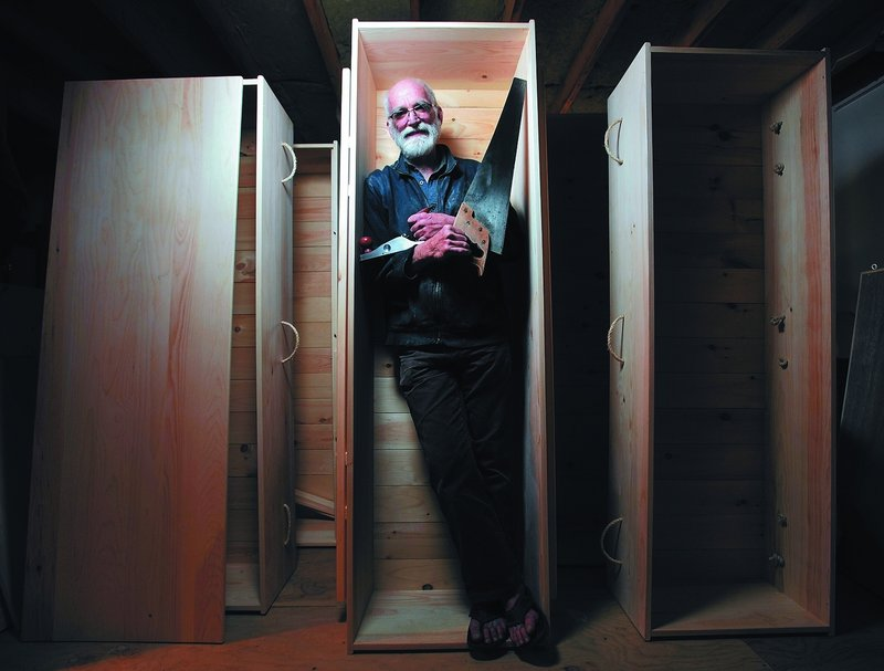 "Chuck Lakin stands inside a coffin in the basement workshop of his Waterville home Saturday. ""Americans are really good at ignoring the fact that they're going to die,"" he said."