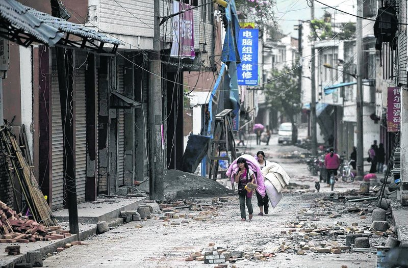 People carrying their belongings walk in quake-damaged Gucheng Village, Longmen Township, Lushan county, in southwest China's Sichuan Province on Saturday.