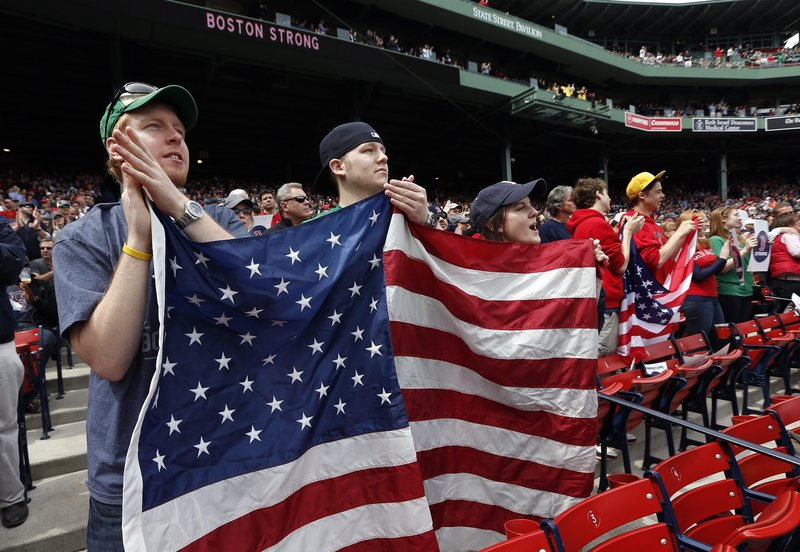 Red Sox fans display an American flag during pregame ceremonies at Fenway Park on Saturday. It was the team's first home game since the Boston Marathon bombings. The Sox planned to autograph their uniforms and auction them off to raise money for a charity to benefit victims of last week's violence.