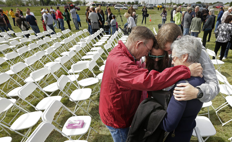 Churchgoers huddle to pray after a service of the First Baptist Church in a field Sunday, four days after an explosion at a fertilizer plant in West, Texas. The congregation could not meet in the church building because it is in the damage zone.