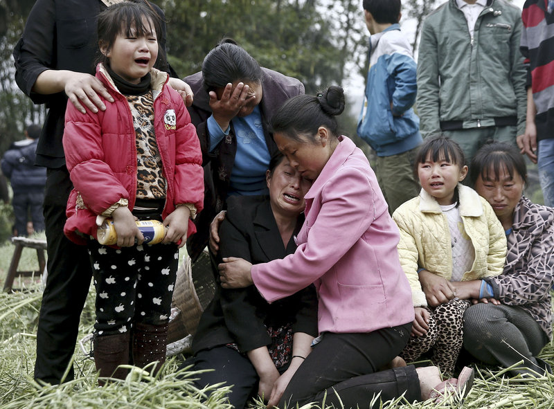 Villagers attending a funeral in Longmen village in Lushan county in southwest China's Sichuan province Sunday cry for their relatives who were killed in an earthquake.