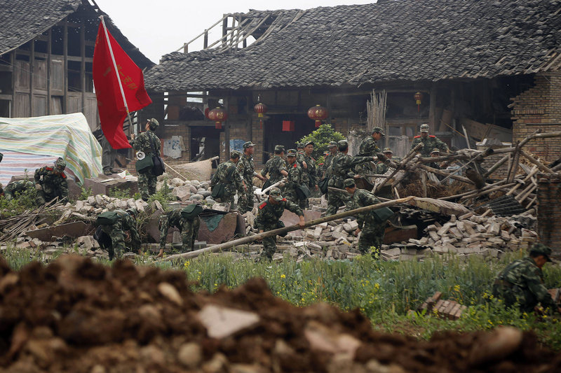 Rescue workers in Qingyan village in southwestern China's Sichuan province search Monday through the rubble of a building that collapsed during Saturday's earthquake.
