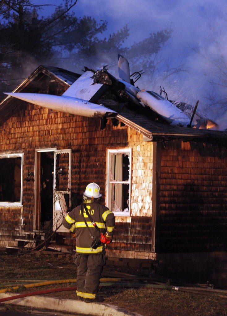 In this 2011 file photo, firefighters extinguish a blaze on Granite Street in Biddeford after a plane crashed into a home. The children of a highly decorated, retired Air Force pilot who died when his civilian plane crashed in Biddeford two years ago, and the couple whose home was destroyed by the crash, are jointly suing the companies that maintained and inspected the plane.